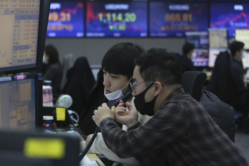 Currency traders watch monitors at the foreign exchange dealing room of the KEB Hana Bank headquarters in Seoul, South Korea, Friday, Nov. 20, 2020. A...