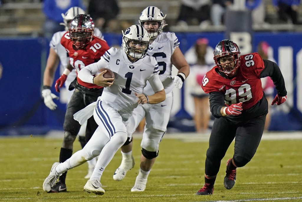 FILE - In this Saturday, Oct. 31, 2020, file pool photo, BYU quarterback Zach Wilson (1) carries the ball in the first half of an NCAA college footbal...