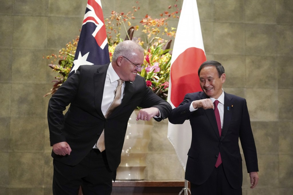 Australian Prime Minister Scott Morrison, left, and Japanese Prime Minister Yoshihide Suga bump elbows to greet prior to the official welcome ceremony...