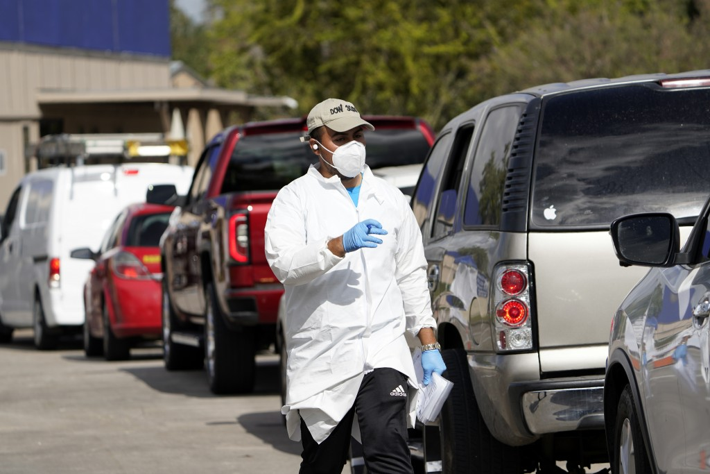 A healthcare worker processes people waiting in line at a United Memorial Medical Center COVID-19 testing site Thursday, Nov. 19, 2020, in Houston. Te...
