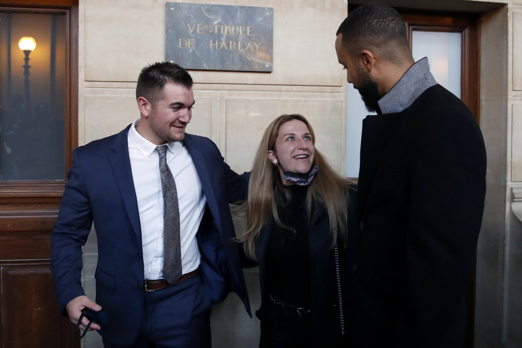 Train host Shauna Asley Verstichelen, center, greets Alek Skarlatos, left, and Anthony Sadler, right, at the end of their hearing during the Thalys at...