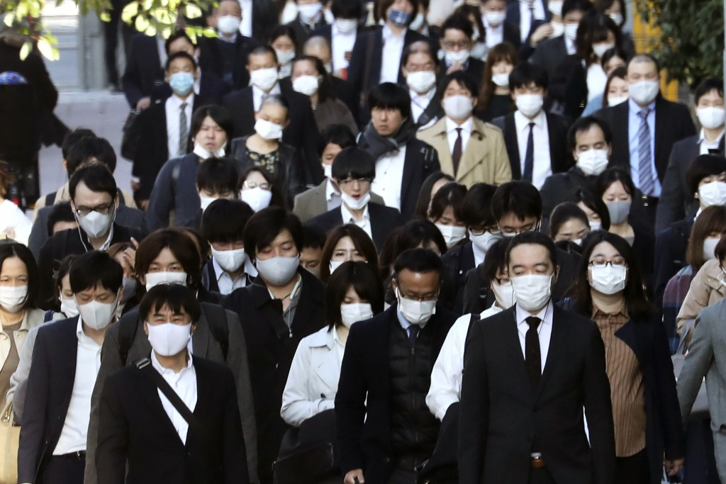 Commuters wearing face masks to protect against the spread of the coronavirus walk along a pedestrian sidewalk in Tokyo, Tuesday, Nov. 17, 2020. (AP P...