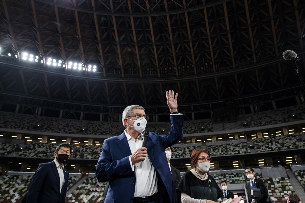 IOC President Thomas Bach wearing a face mask waves as he speaks to the media at the National Stadium, the main venue for the 2020 Olympic and Paralym...