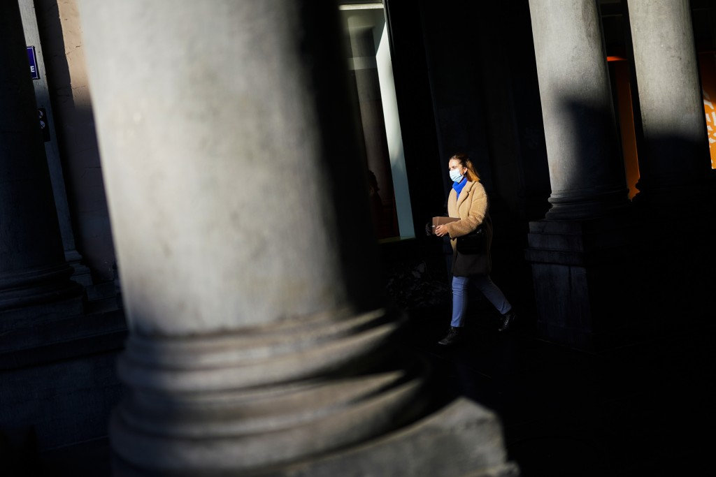 A woman, wearing a face mask to prevent the spread of the coronavirus COVID-19, walks along a commercial street in downtown Brussels, Friday, Nov. 20,...