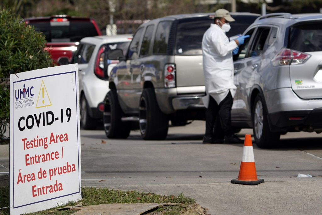 A healthcare worker processes people waiting in line at a United Memorial Medical Center COVID-19 testing site Thursday, Nov. 19, 2020, in Houston.  T...