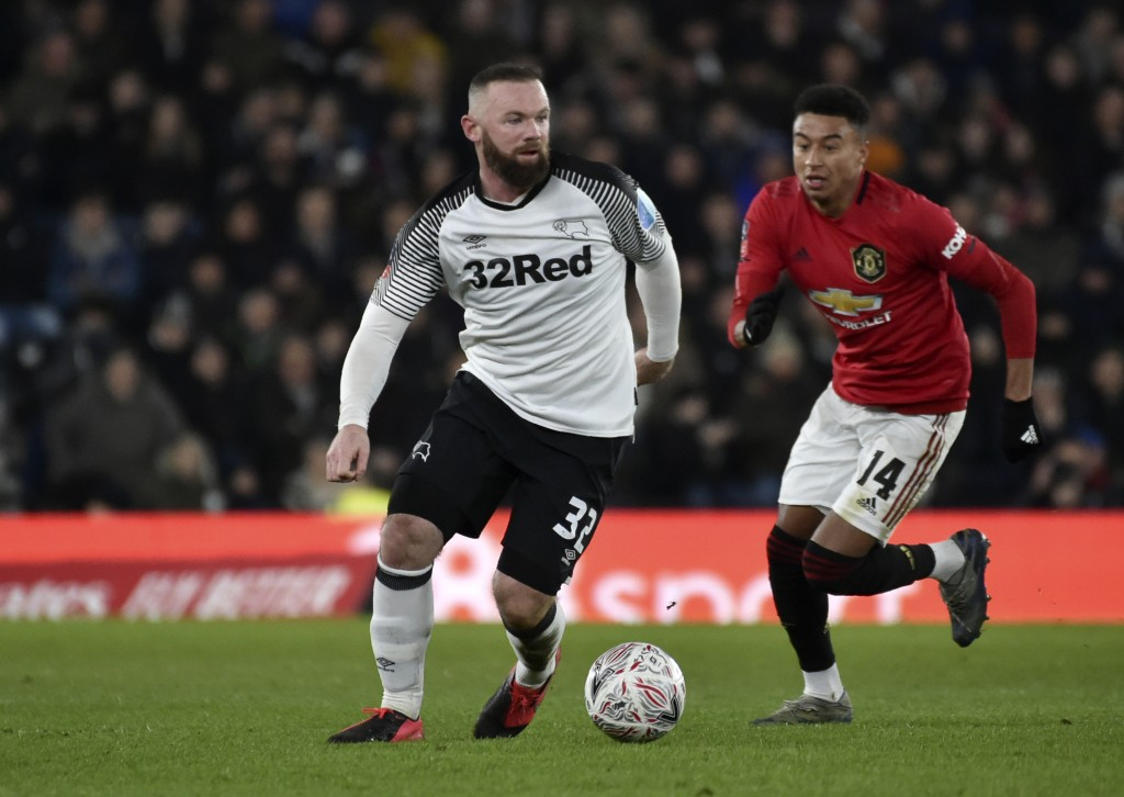 FILE - In this Thursday, March 5, 2020 file photo, Derby's Wayne Rooney, left, and Manchester United's Jesse Lindgard run for the ball during the FA C...