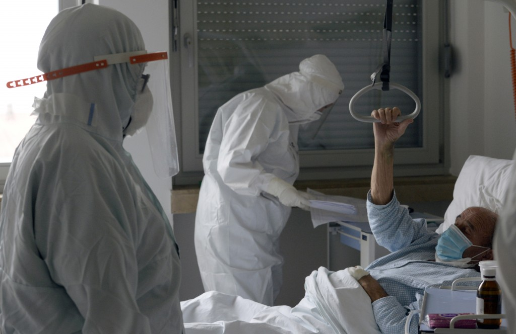 A doctor and nurse take care of patients with COVID-19 at a former military hospital in the capital Sarajevo, Bosnia, Thursday, Nov. 19, 2020. Doctors...