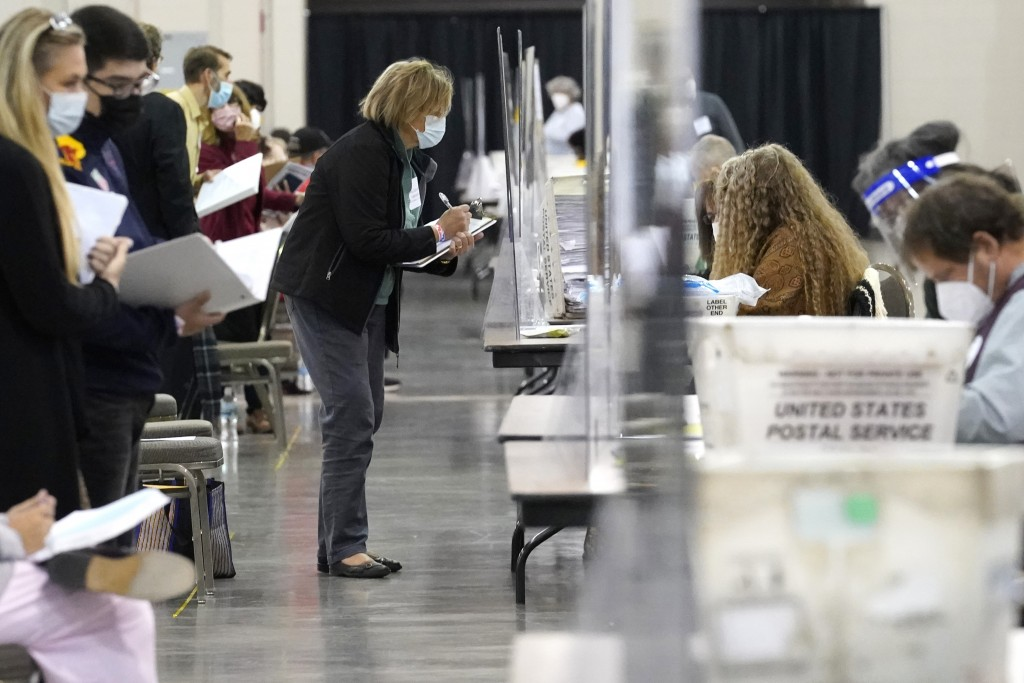 Recount observers watch ballots during a Milwaukee hand recount of Presidential votes at the Wisconsin Center, Friday, Nov. 20, 2020, in Milwaukee, Wi...