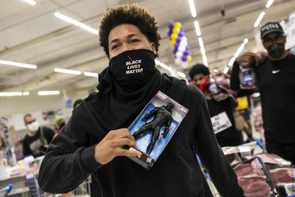 A Black Lives Matter activist holds a Black Panther doll inside a Carrefour supermarket during a demonstration against the murder of Black man Joao Al...