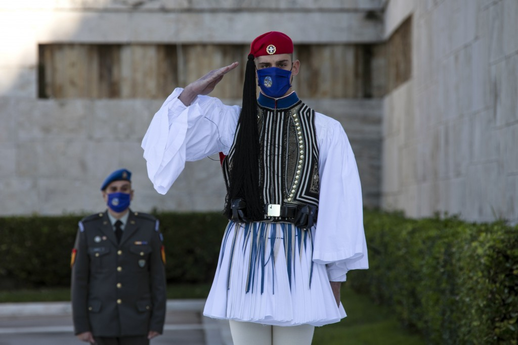 A Greek Presidential Guard, wearing a protective mask against the spread of coronavirus, salutes during a wreath laying ceremony, in Athens, Saturday,...