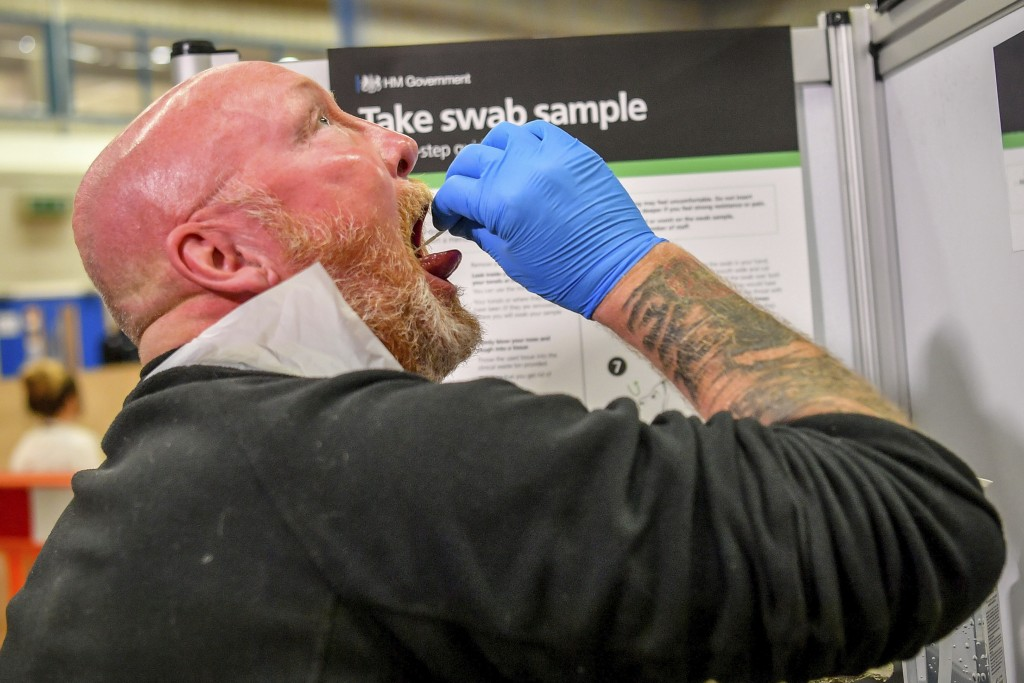 A testing staff member completes a lateral flow test swab, mandatory before opening to the public, at Rhydycar leisure centre in Merthyr Tydfil, Wales...