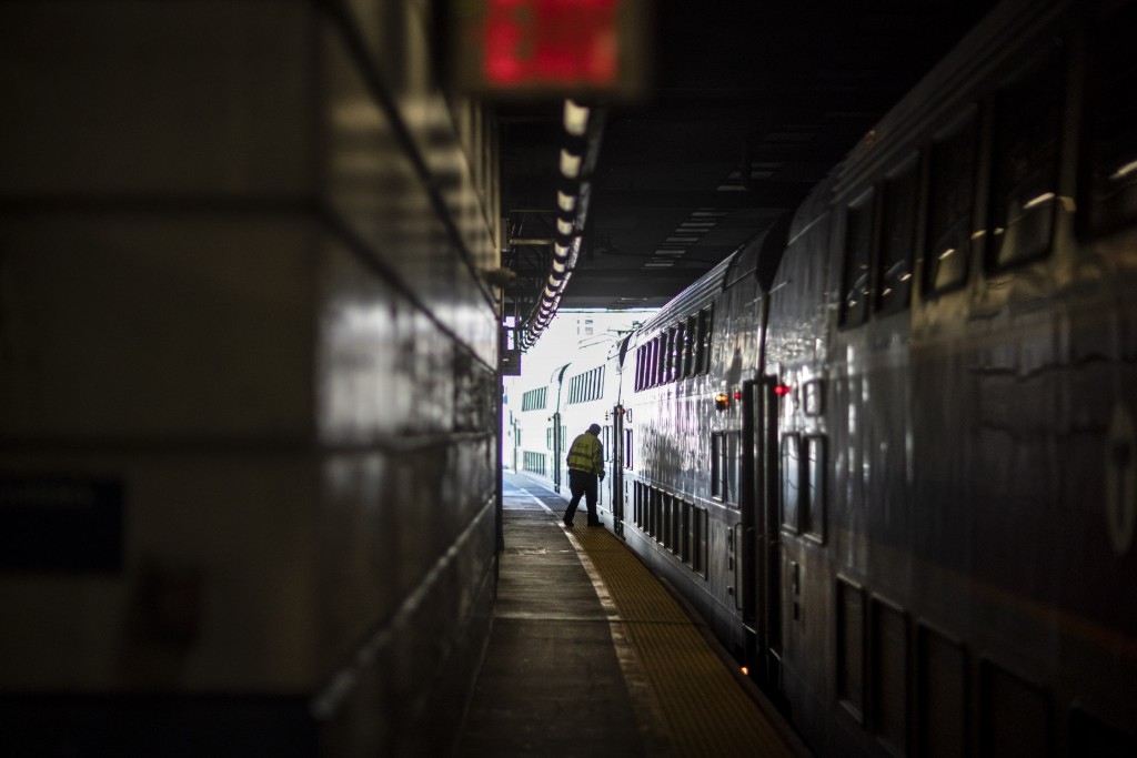 A train employee boards the commuter rail heading to Boston after waiting for passengers, Friday, Nov. 20, 2020, in Providence, R.I. With the coronavi...