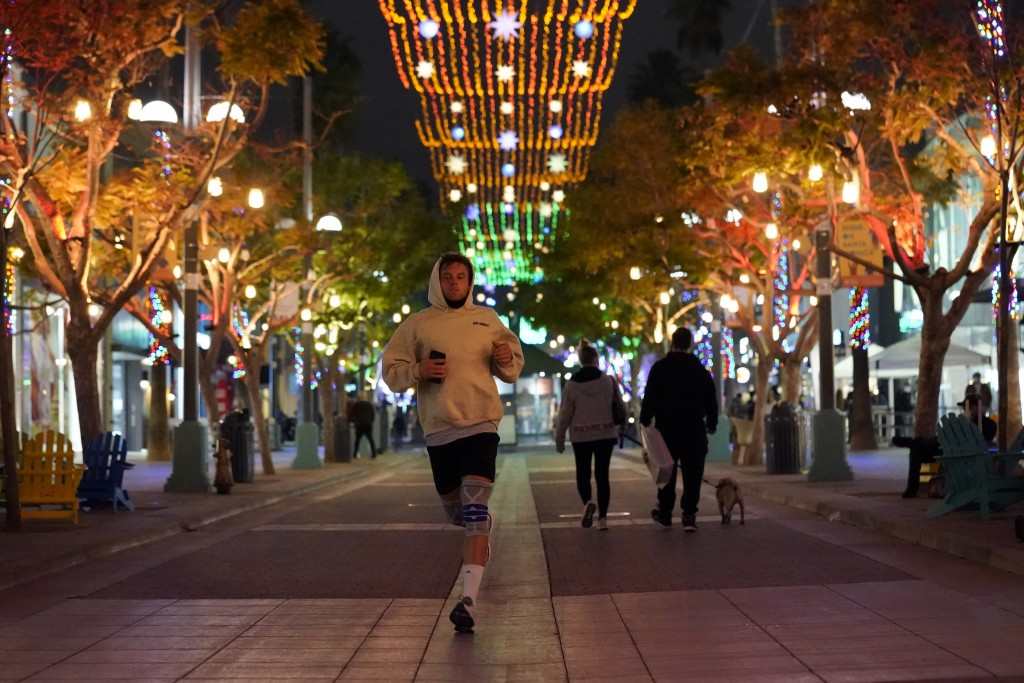 FILE - In this Nov. 19, 2020, a jogger runs through a shopping district in Santa Monica, Calif. California Gov. Gavin Newsom is imposing an overnight ...