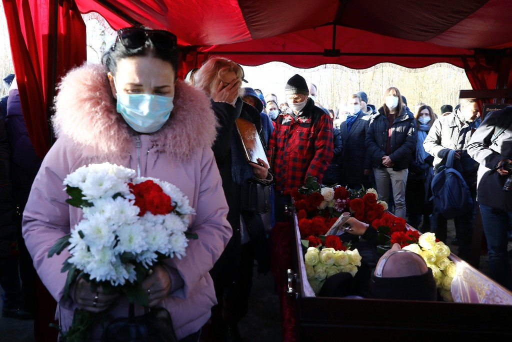 People cry and hold flowers as they pay their respects at the coffin of Roman Bondarenko, an anti-government protester who died in hospital following ...