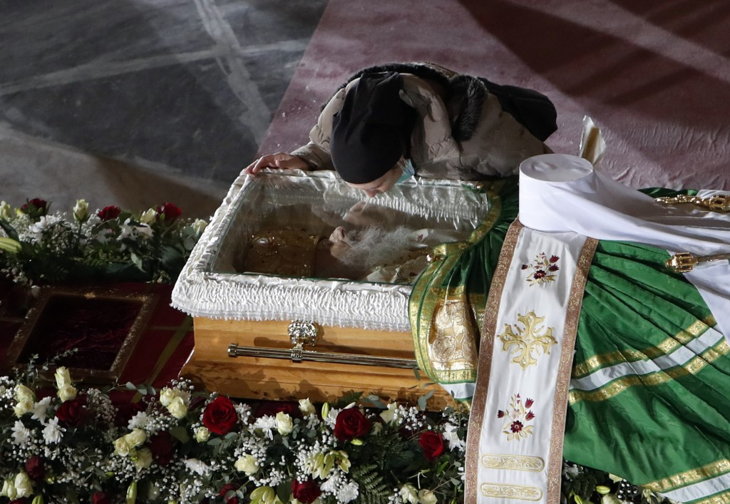A woman kisses the coffin of Patriarch Irinej as he lies in repose at the St. Sava Temple in Belgrade, Serbia, Saturday, Nov. 21, 2020. Patriarch Irin...