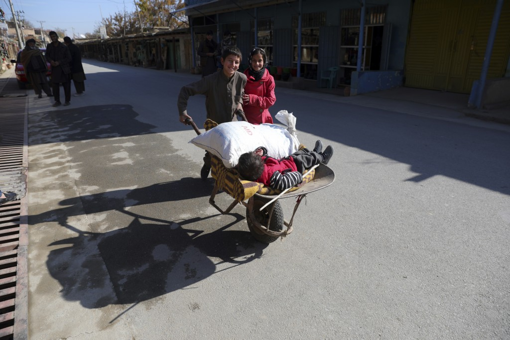 An Afghan boy and his sister use a wheelbarrow to move their brother in Istalef district of Kabul, Afghanistan, Saturday, Nov. 21, 2020. (AP Photo/Rah...