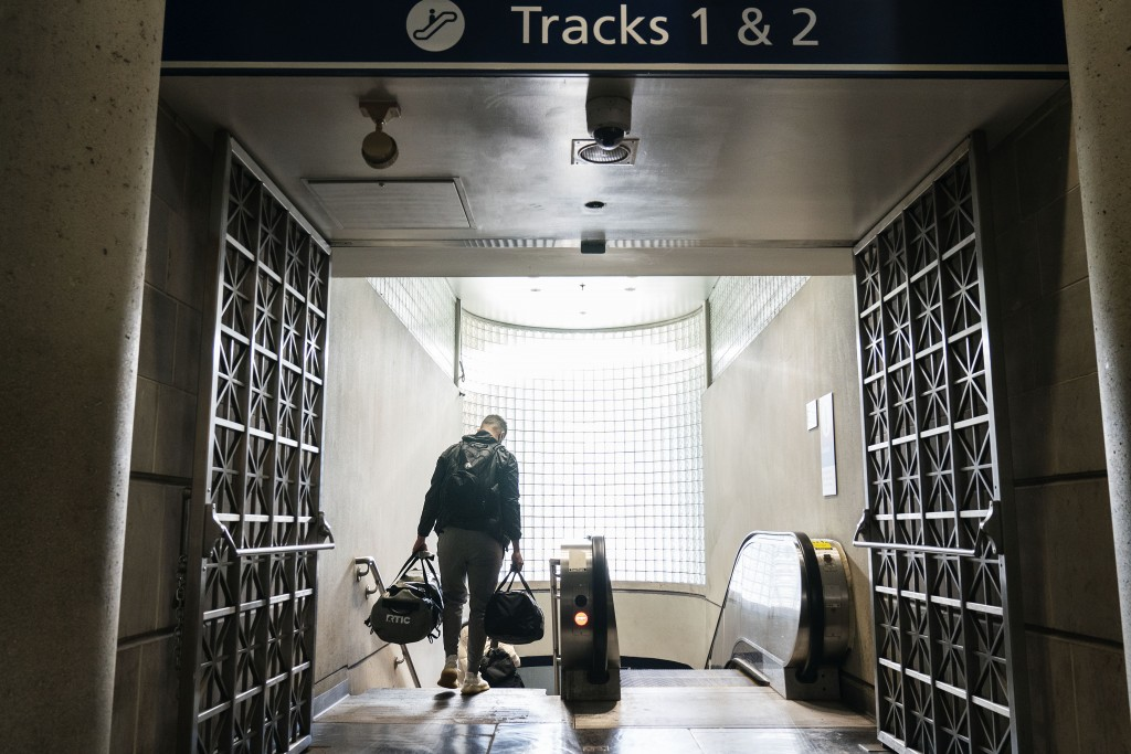 A passenger descends a staircase to board an Amtrak train, Friday, Nov. 20, 2020, in Providence, R.I. With the coronavirus surging out of control, the...