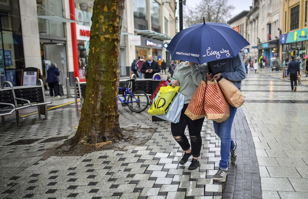Shoppers loaded with bags and an umbrella to protect against the falling rain, in the centre of Cardiff, Wales, Friday Nov. 20, 2020, where shops are ...