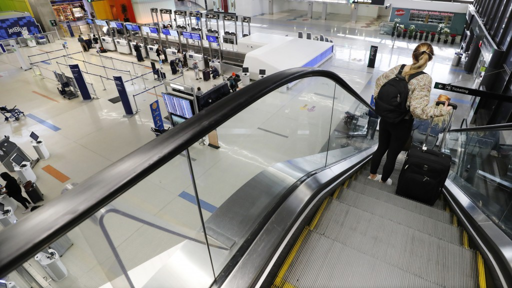 A traveler rides an escalator with her luggage as she arrives at the nearly empty JetBlue terminal at Logan Airport, Friday Nov. 20, 2020, in Boston. ...