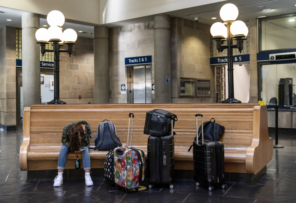 A passenger waits to board a train at the station in Providence, R.I., Friday, Nov. 20, 2020. With the coronavirus surging out of control, the nation'...