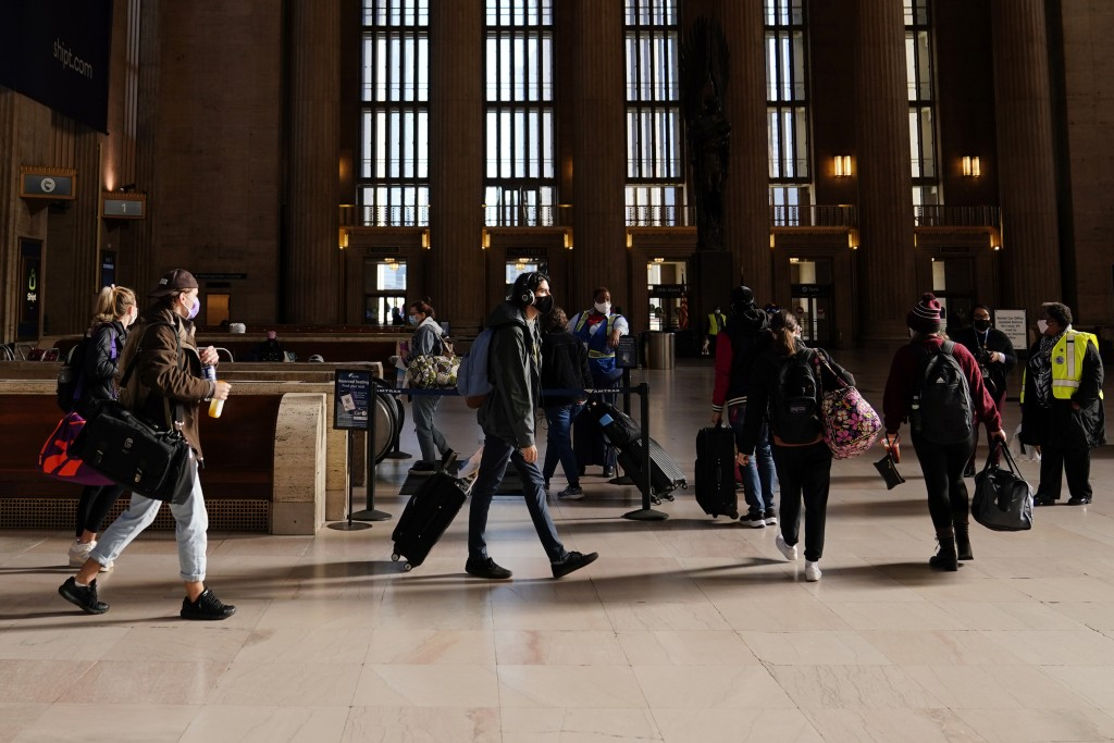Travelers wait in line to board a train at the 30th Street Station ahead of the Thanksgiving holiday, Friday, Nov. 20, 2020, in Philadelphia. With the...