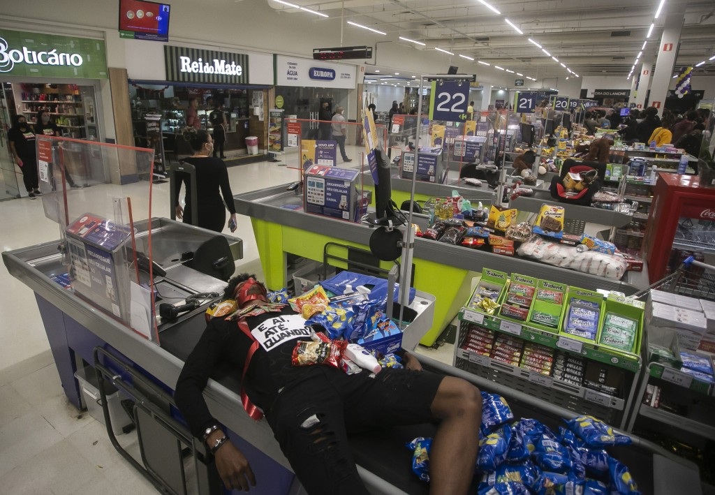 Jonata Anjo lies on a checkout counter at a Carrefour supermarket during a protest against the murder of Black man Joao Alberto Silveira Freitas at a ...