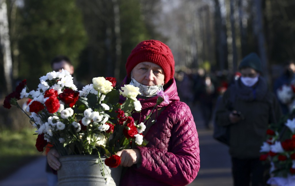 People carry flowers to pay their respects to Roman Bondarenko, an anti-government protester who died in hospital following what witnesses said was a ...