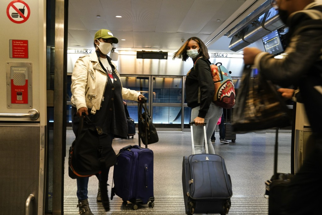 Travelers leave the AirTrain at JKF International Airport Friday, Nov. 20, 2020, in New York. Rising U.S. coronavirus cases, a new round of state lock...