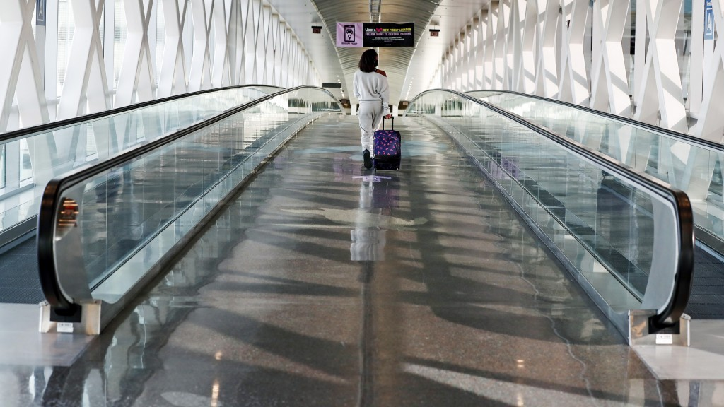 A traveler walks with her luggage across a nearly empty skyway bridge at Logan Airport, Friday Nov. 20, 2020, in Boston. With the coronavirus surging ...