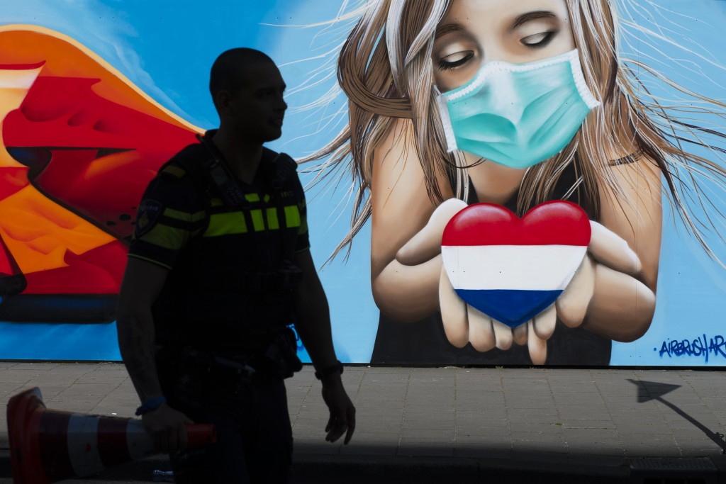FILE - In this file photo dated Friday, April 24, 2020, a police officer is silhouetted as he passes a mural by artist Casper Cruse, showing a woman w...