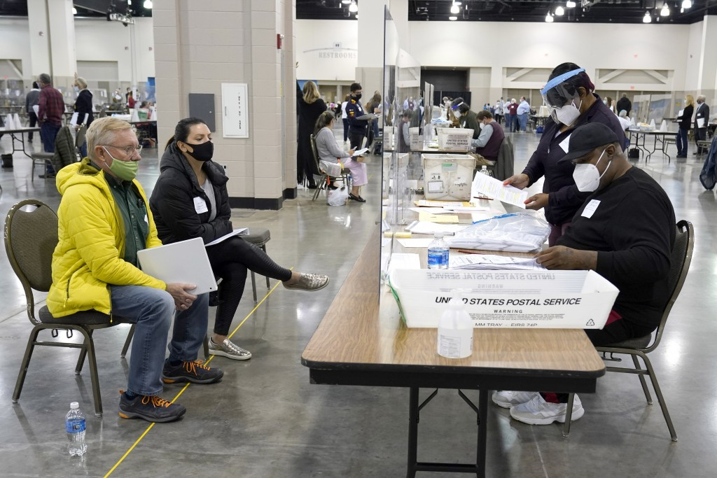 Election workers, right, verify ballots as recount observers, left, watch during a Milwaukee hand recount of presidential votes at the Wisconsin Cente...