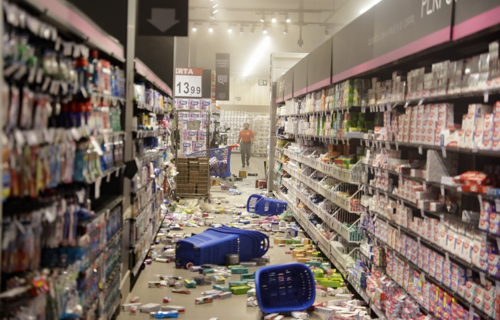 Products knocked off shelves by protesters litter an aisle at a Carrefour supermarket during a protest against the murder of Black man Joao Alberto Si...