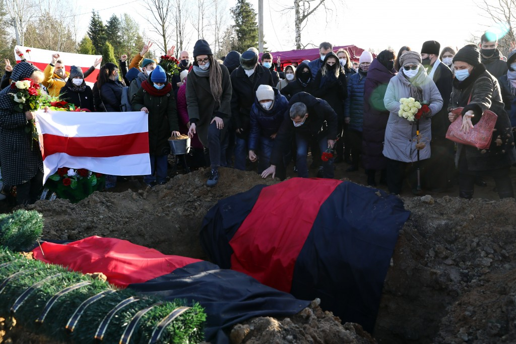 People cry and hold flowers as they pay their respects at the grave of Roman Bondarenko, an anti-government protester who died in hospital following w...
