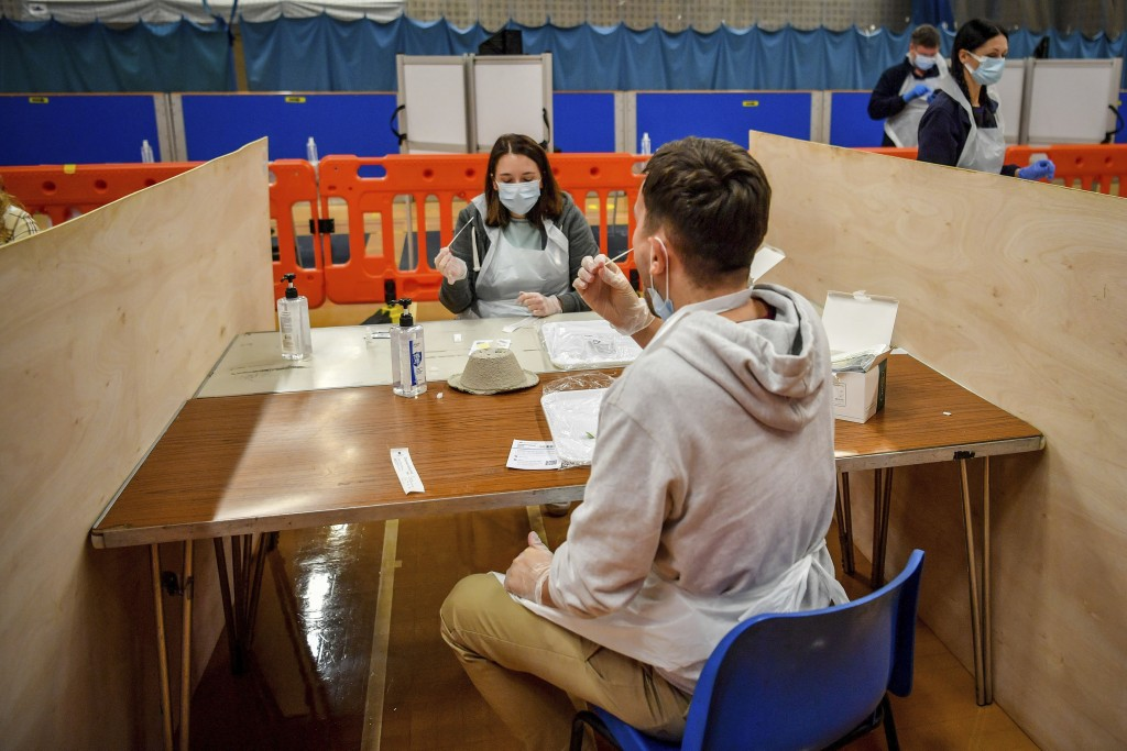 Testing staff members complete lateral flow test swabs, mandatory before opening to the public, at Rhydycar leisure centre in Merthyr Tydfil, Wales, S...