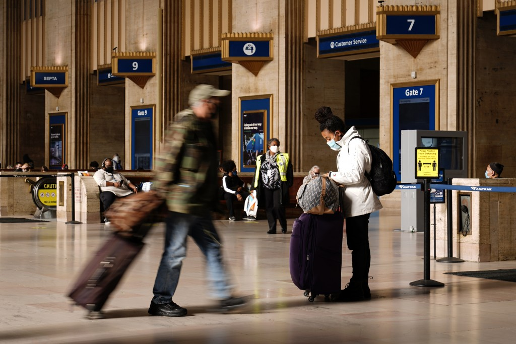 Travelers make their way through the 30th Street Station ahead of the Thanksgiving holiday, Friday, Nov. 20, 2020, in Philadelphia. With the coronavir...