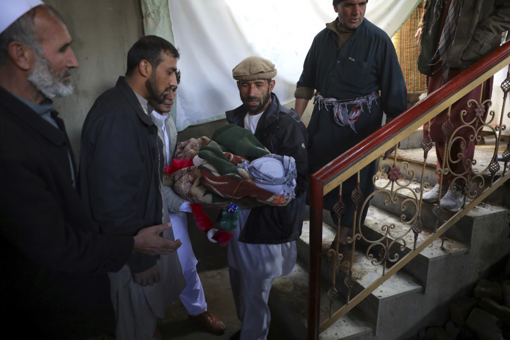 Relatives carry the dead body of a boy who was killed by a mortar shell attack in Kabul, Afghanistan, Saturday, Nov. 21, 2020. Mortar shells slammed i...