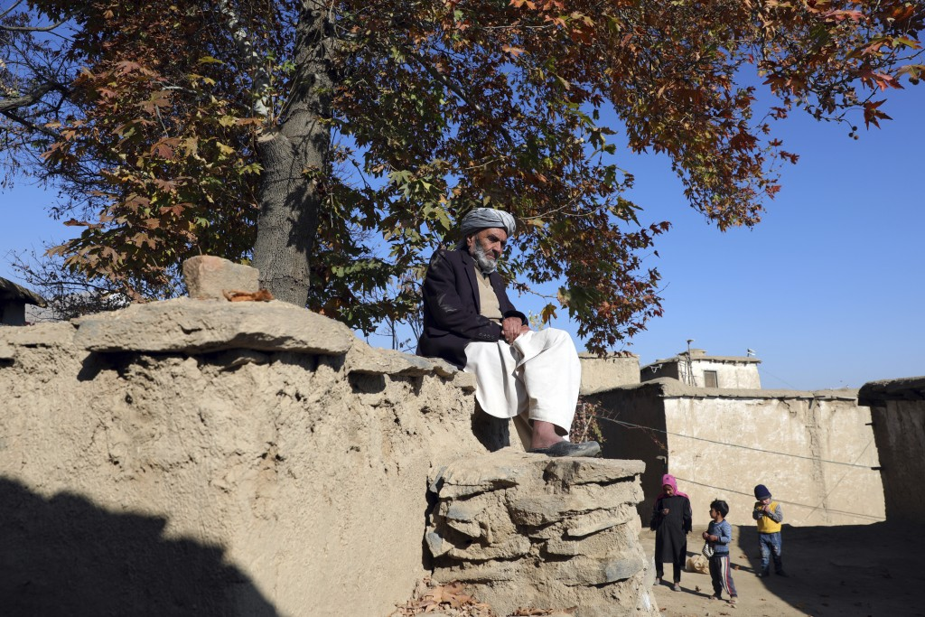 An elderly Afghan man sits in the sun on a cold day in Istalef district of Kabul, Afghanistan, Saturday, Nov. 21, 2020. (AP Photo/Rahmat Gul)