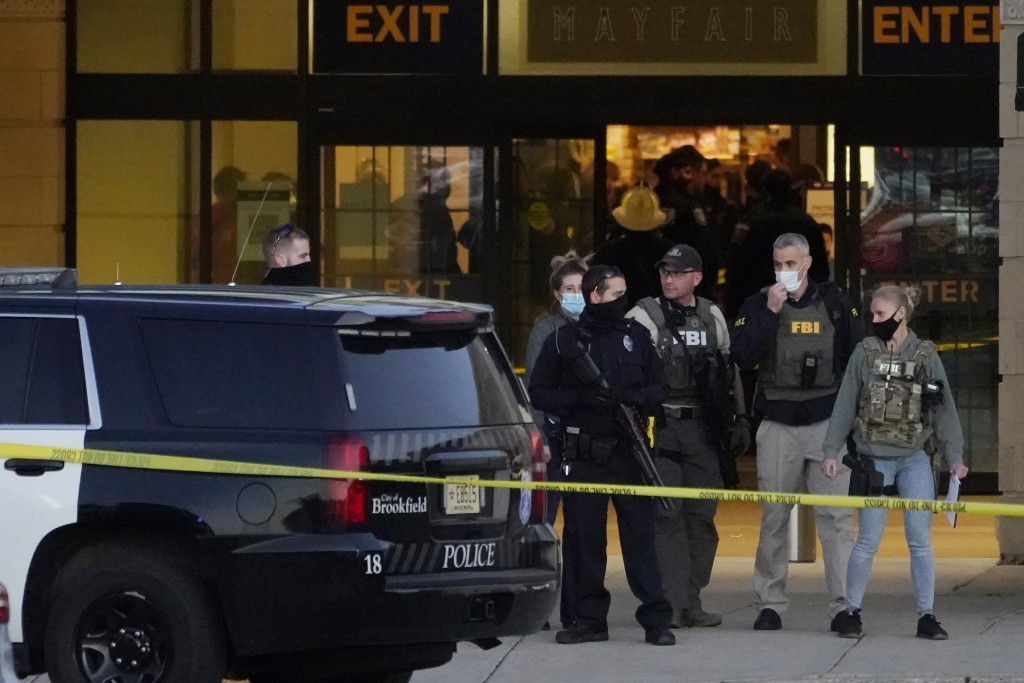FBI officials and police stand outside the Mayfair Mall after a shooting, Friday, Nov. 20, 2020, in Wauwatosa, Wis. Multiple people were shot Friday a...