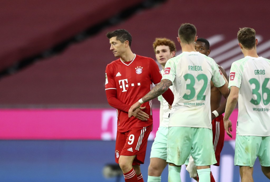 Bayern's Robert Lewandowski, left, and Bremen's Marco Friedl, second left, leave the field after the German Bundesliga soccer match between FC Bayern ...