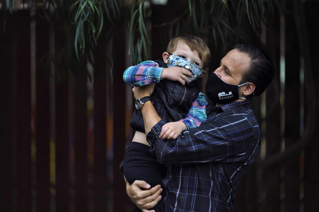 Nicholas Philbrook, right, holds his son Andrew, 4, in his backyard, Wednesday, Nov. 18, 2020, in Camarillo, Calif. Philbrook has been trying to convi...
