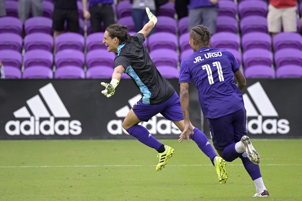 Orlando City defender Rodrigo Schlegel, left, celebrates after blocking the final New York City FC penalty kick during overtime of an MLS soccer playo...