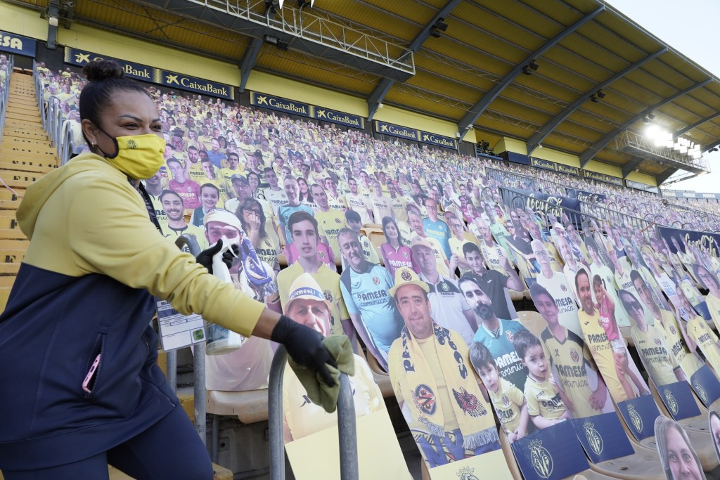 A stadium members cleans the stands as cardboard cut-out of fans are placed on the seats ahead of the Spanish La Liga soccer match between Villarreal ...