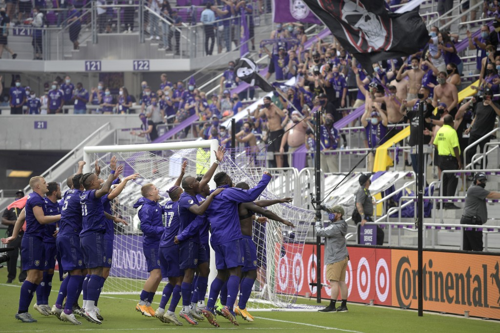 Orlando City players celebrate in front of fans after defeating New York City FC on penalty kicks in an MLS soccer playoff match, Saturday, Nov. 21, 2...