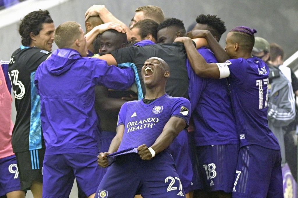 Orlando City defender Kamal Miller (27) and teammates celebrate after defeating New York City FC on penalty kicks in an MLS soccer playoff match, Satu...