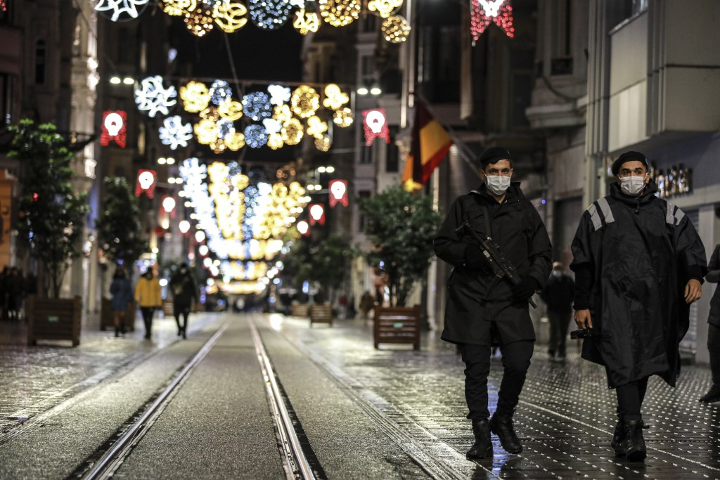Police officers patrol Istiklal street, the main shopping street in Istanbul, minutes into the lockdown, part of the new measures to try curb the spre...