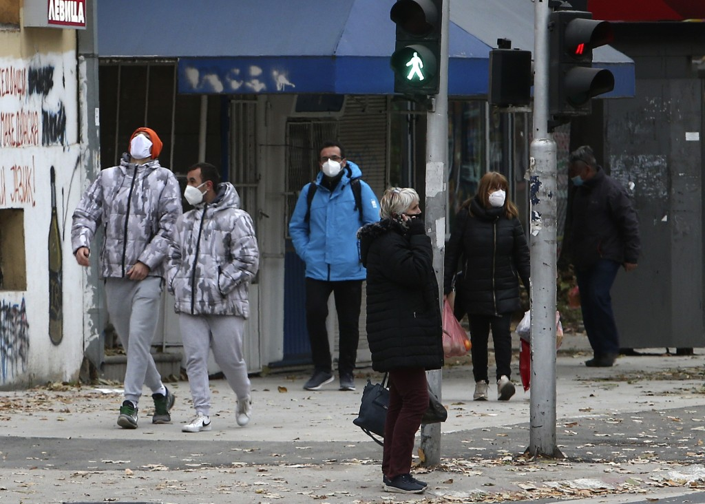 People wearing face masks walk through a street in Skopje, North Macedonia, Saturday, Nov. 21, 2020. North Macedonia has declared its first-ever natio...