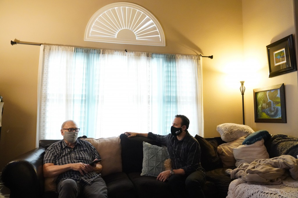 Nicholas Philbrook, right, talks to his father-in-law, Raymond Schmidt, at home, Wednesday, Nov. 18, 2020, in Camarillo, Calif. Philbrook has been try...