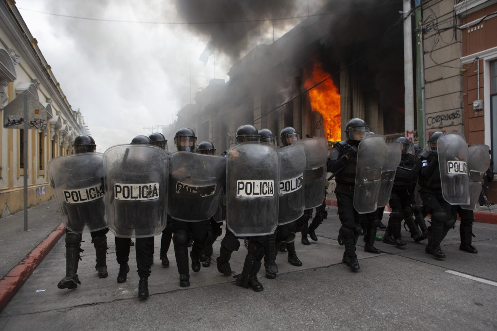 Riot police form a cordon as flames shoot out from the Congress building after protesters set a part of the building on fire, in Guatemala City, Satur...