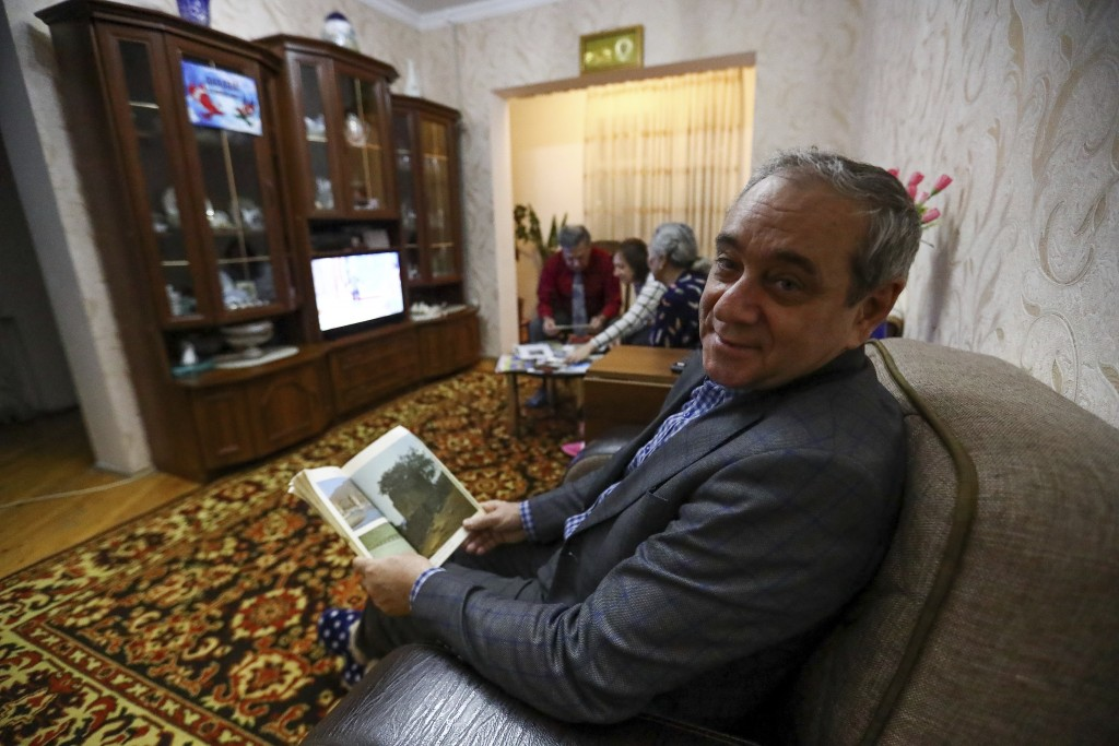 Adil Sharifov poses for a photo at home in Baku, Azerbaijan, Friday, Nov. 20, 2020. Adil Sharifov, 62, who left his hometown in 1992 during the first ...