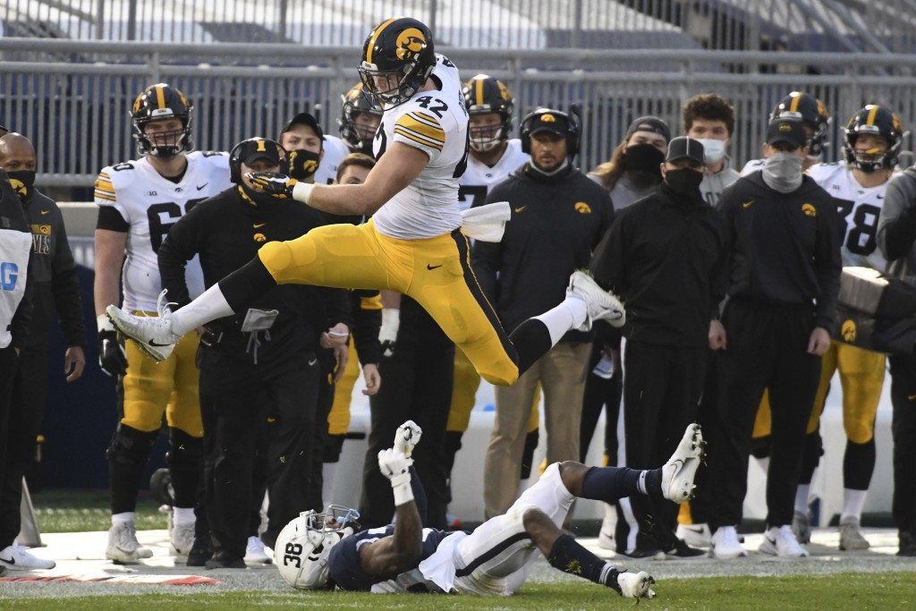 Iowa tight end Shaun Beyer (42) hurdles Penn State safety Lamont Wade (38) in the first quarter of an NCAA college football game in State College, Pa....